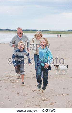 Grandparents And Grandchildren Running Along Beach Together - Stock Photo