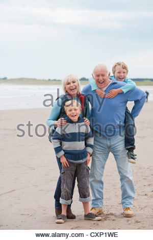 Grandparents And Grandchildren Walking Along Beach Together - Stock Photo