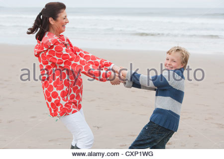 Grandmother And Grandson Walking Along Beach Together - Stock Photo
