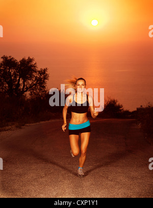 Image of of sporty blond female running along the road over sunset, slim athletic woman run in marathon, active - Stock Photo