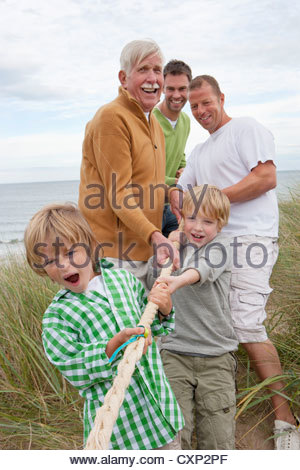 Male Family Members Taking Part In Tug Of War Match On Beach - Stock Photo