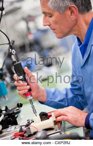 Technician working in hi-tech electronics manufacturing plant - Stock Photo