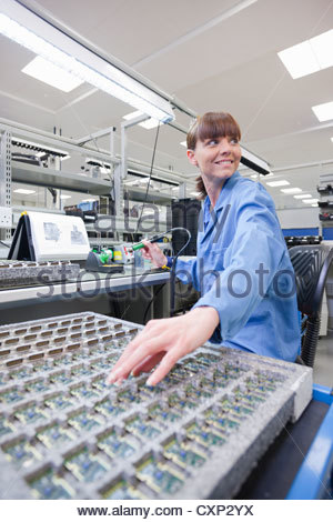 Technician working on assembly line in hi-tech electronics manufacturing plant - Stock Photo