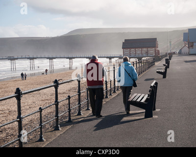A retired couple enjoying warm autumn sunshine strolling on the deserted promenade at Saltburn - Stock Photo