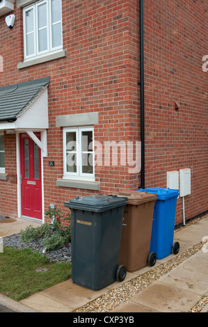 Assortment of wheelie bins lined up on a drive outside a house in England. - Stock Photo