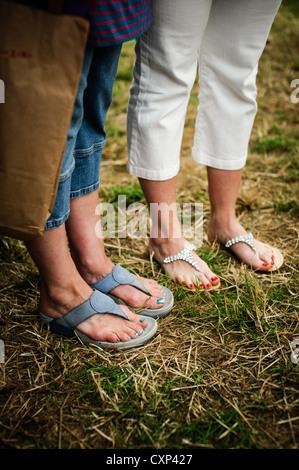 Two women's feet wearing sandals