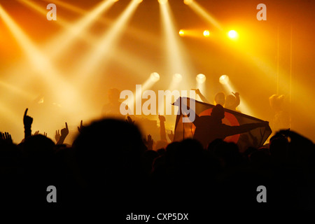 Silhouetted spectators / crowd and ambiance during live rock concert with rockers on stage illuminated by spotlights - Stock Photo