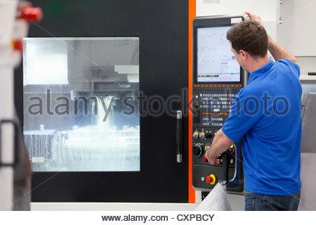 Technician operating lathe cutting machine in hi-tech manufacturing plant - Stock Photo
