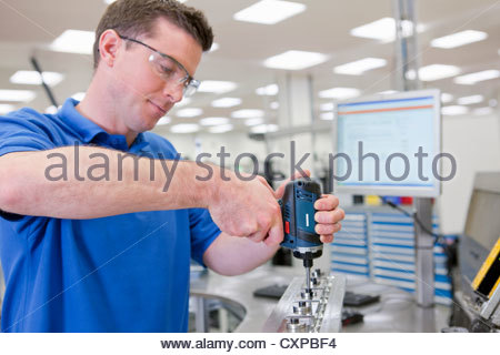 Technician assembling product in hi-tech manufacturing plant - Stock Photo