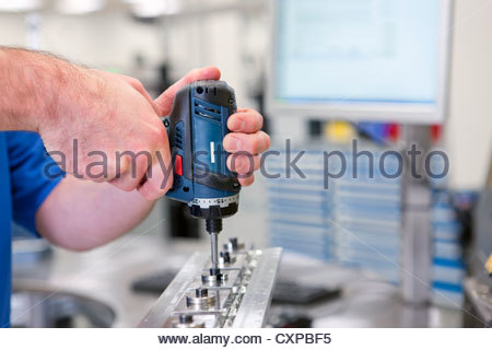 Close up of technician assembling product in hi-tech manufacturing plant - Stock Photo