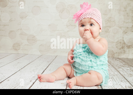 6 month old baby girl sits on a wooden floor with white peeling paint. She has on a turquoise ruffled bloomer and - Stock Photo