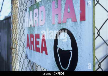 Close up of weathered sign on wire mesh fence stating Hard Hat Area with icon of head wearing hard hat - Stock Photo