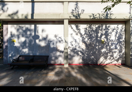 A wooden bench standing on pavement against a grey wall with sharp shadows of trees across it - Stock Photo