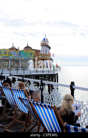 Helter Skelter on Brighton pier and holiday makers - Stock Photo