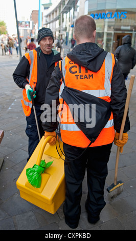 Two city street cleaners in high visibilty day-glow vests holding brooms. - Stock Photo