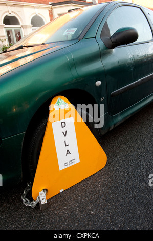 DVLA wheel clamp on a untaxed car parked on a street in England. - Stock Photo