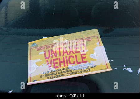 Sticker on the windscreen of an untaxed vehicle that has been wheelclamped on a street in England. - Stock Photo