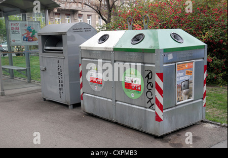 A pair of metal recycling bins (for clear & coloured glass and clothing & shoe) in a residential area of Vienna - Stock Photo