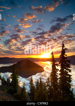 Sunrise on Crater Lake with Wizard Island. Crater Lake National Park. Oregon reflection,sun,silhouette,forest, - Stock Photo