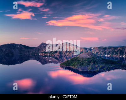 Crater Lake with Wizard Island at sunrise . Crater Lake National Park, Oregon, sunrise clouds reflecting in calm - Stock Photo