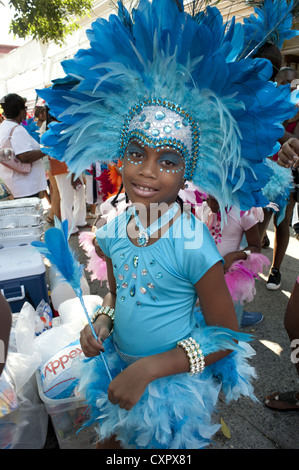 USA: Brooklyn, New York. Caribbean Kiddies Day parade, Crown Heights. Girl in blue, feathered costume, 2012. - Stock Photo
