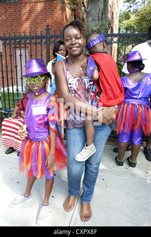 USA: Brooklyn, NY. Mother and her two, costumed children wait to march in The Caribbean Kiddies Day Parade, 2012. - Stock Photo