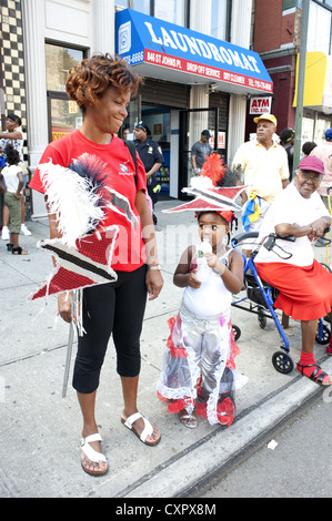 U.S.A.: Brooklyn, NY. Girl representing Trinidad and Tobago and her mom take a break during the Caribbean Kiddies - Stock Photo