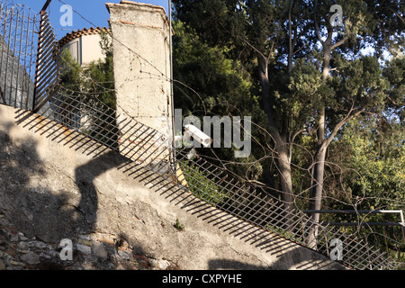 Surveillance Camera on a stone wall with barbed fence - Stock Photo