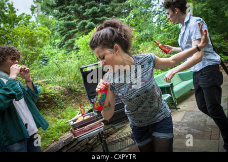 Young woman singing into bottle at a backyard barbecue - Stock Photo