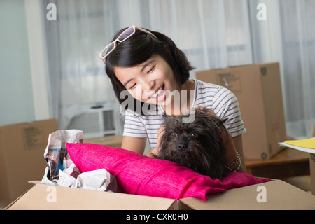 Young woman with pet dog in moving box - Stock Photo