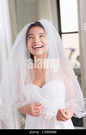 Young woman wearing wedding dress and laughing - Stock Photo