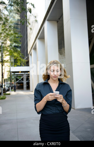 Businesswoman walking and texting on cellphone - Stock Photo