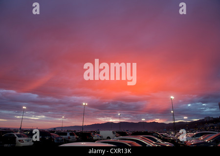 Cars in parking lot at sunset - Stock Photo
