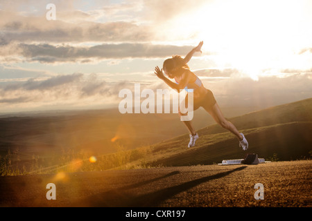 Young woman moving off starting blocks in rural setting - Stock Photo