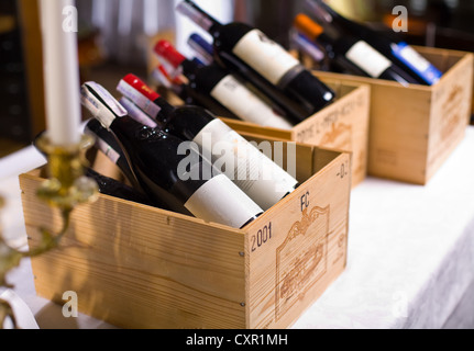 Wine bottles in wooden boxes are on the table restaurant. - Stock Photo