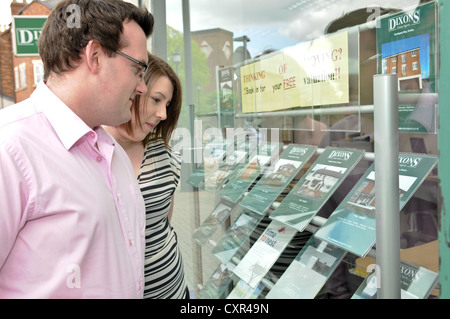 Young white couple looking in for houses in an estate agents window, pointing at properties and holding a set of - Stock Photo