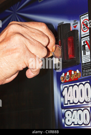 A man's hand is inserting a euro coin into a slot machine, warning sign, addiction to gambling - Stock Photo