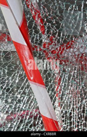 Barrier tape, broken store window, vandalism - Stock Photo