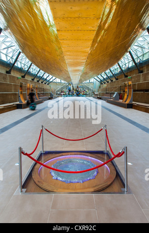 View from underneath the golden hull of the Cutty Sark showing a central display cordoned off . - Stock Photo