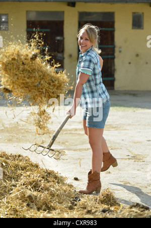 Young female farmer, pitchfork, horse manure, cleaning out with gusto, Gingen, Baden-Wuerttemberg, Germany, Europe - Stock Photo