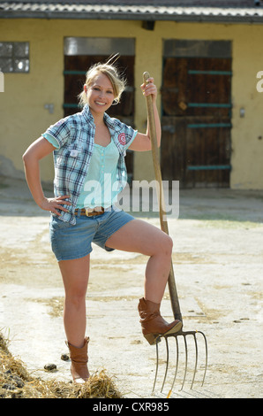 Young female farmer, pitchfork, horse manure, cleaning out, Gingen, Baden-Wuerttemberg, Germany, Europe - Stock Photo