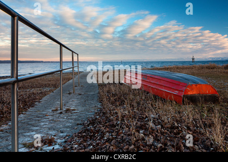 Red lifeboat lying upside down on the shore of Lake Constance near Hoernle mountain, Constance, Konstanz, Baden - Stock Photo