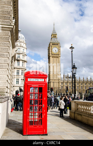 Red telephone booth in front of the clock or bell tower, Big Ben, of the Houses or Parliament, London, South England, - Stock Photo
