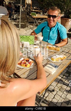 Couple taking a break from cycling at a cafe, province of Bolzano-Bozen, Italy, Europe - Stock Photo