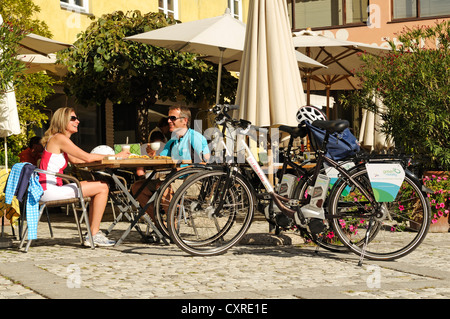 Couple with electric bicycles taking a break at a cafe, province of Bolzano-Bozen, Italy, Europe - Stock Photo