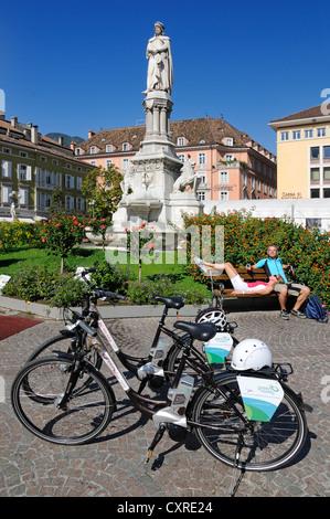 Couple with electric bicycles taking a break, Walther square, Bolzano, province of Bolzano-Bozen, Italy, Europe - Stock Photo