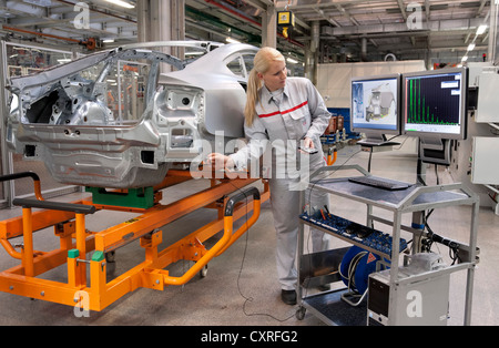 An Audi employee checking welding spots on a car body set by robots with a sensor, Audi plant in , Bavaria - Stock Photo
