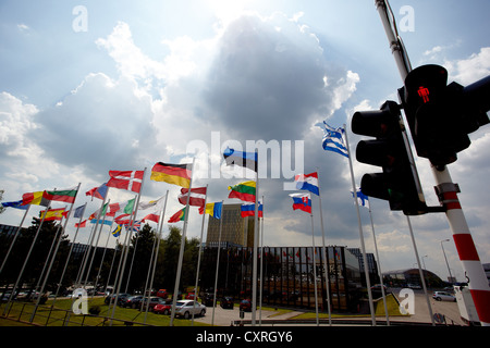 Red traffic lights in front of the national flags of the member states of the European Union, building of the European - Stock Photo