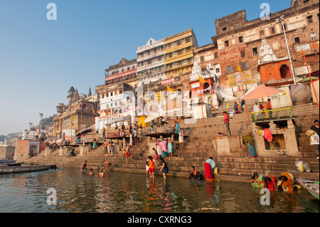 Bathers, boats, Ghats, holy stairs leading to the Ganges, city view in the early morning, Varanasi, Benares or Kashi - Stock Photo
