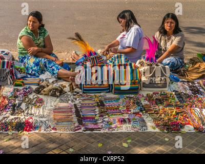 Three indigenous women sell their weavings and handicrafts on the street in Asunción, Paraguay. - Stock Photo